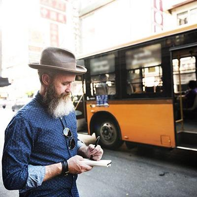 BUS, HAT, WRITING, NOTEBOOK, LEFTHANDED, MAN, PAGE, BEARD, WRISTWATCH, SHIRT, WINDOW