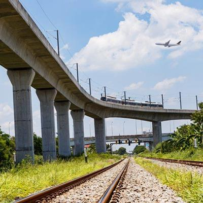 PLANE, TRAIN, CLOUDS, RAILS, CARRIAGE, OVERPASS, TRACK, GRAVEL, GRASS, CONCRETE, SUPPORTS, BRIDGE